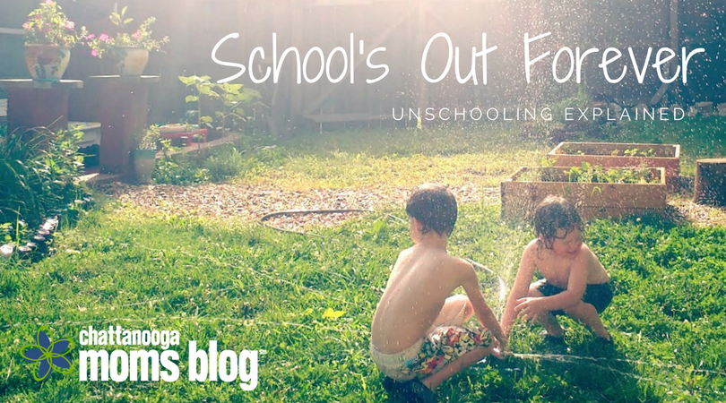 "Image of brothers in bathings suits playing with the sprinklers in their backyard. The title, ""School's Out Forever: Unschooling Explained"" is written on top."