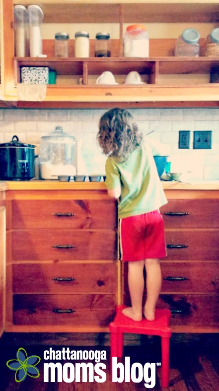 Image of an unschooling three year old standing on a red stool at the kitchen counter and mixing up corn muffins for dinner.