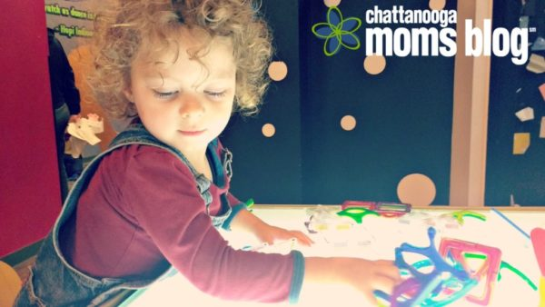 Image of toddler playing with a light table and magnetic blocks at a children's museum