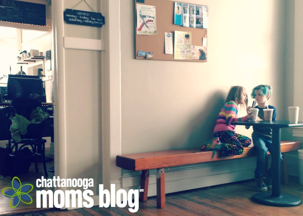 Image of unschooling friends looking at Pokemon cards on a bench outside a coffee shop