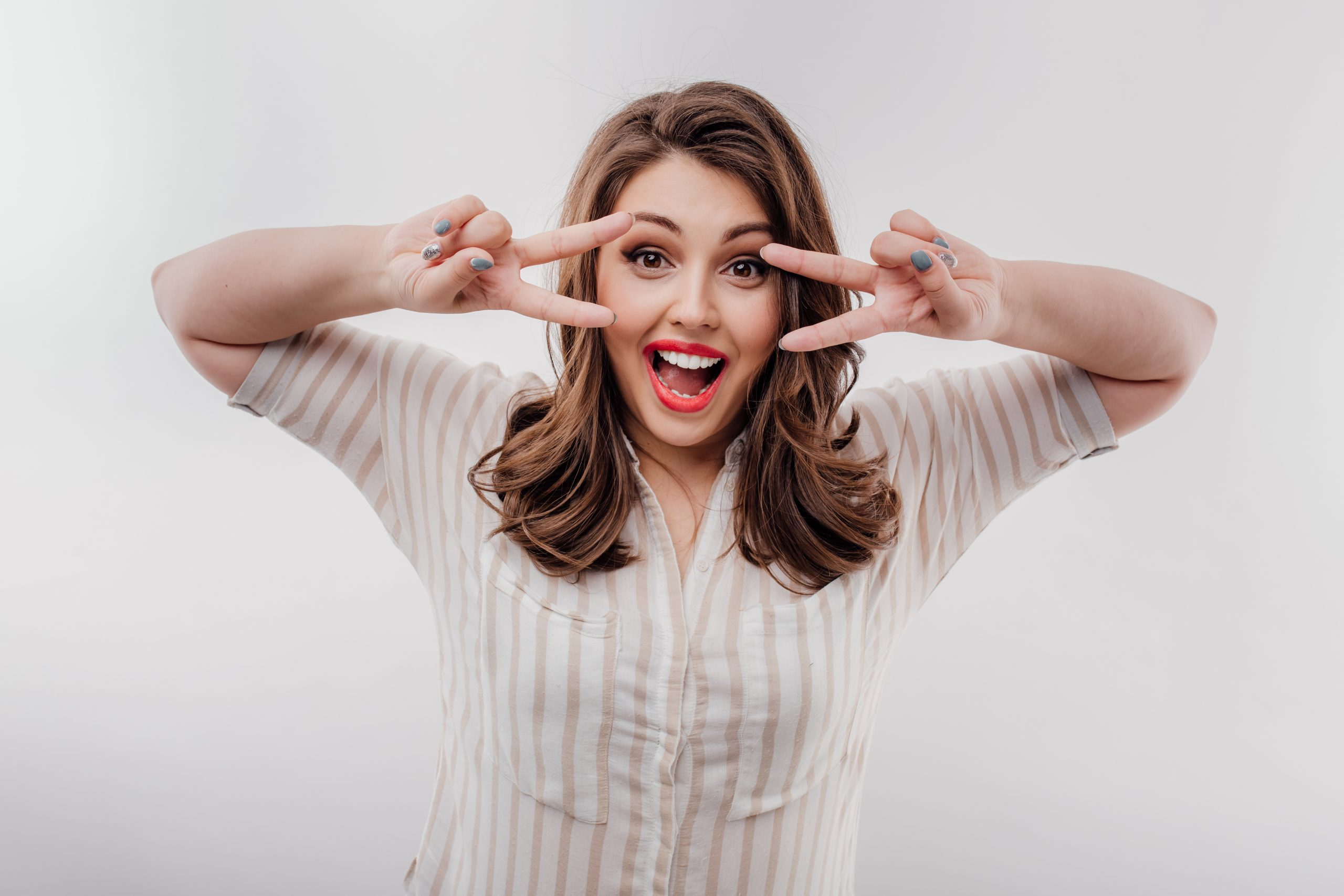 Excited plus size female gesturing V sign